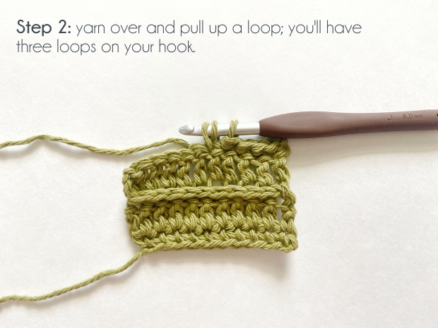 "A swatch of green yarn with a half completed row of the yarn over slip stitch, and a hook with three loops on it.  ""Step 2: yarn over and pull up a loop; you'll have 3 loops on your hook."""