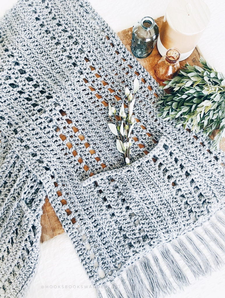 A gray, crocheted pocket-scarf with flowers peeking out of the pocket is laid on a wood board with amber and blue glass bud vases, ceramic jar, and greenery on a white bed spread